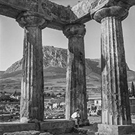 Corinth 1961.  Charles McCabe at the Temple of Apollo.  Acrocorinth in background.