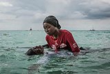Swim instructor Siti, 24, helps a girl float in the Indian Ocean off of Nungwi, Zanzibar, 2017
