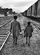 Linda Brown, who was refused admission to a white elementary school, and her 6-yr-old sister Terry Lynn walking along railroad tracks to bus which will take them to segregated Monroe Elementary School during the landmark Brown vs. Board of Education case, Topeka, Kansas, 1953